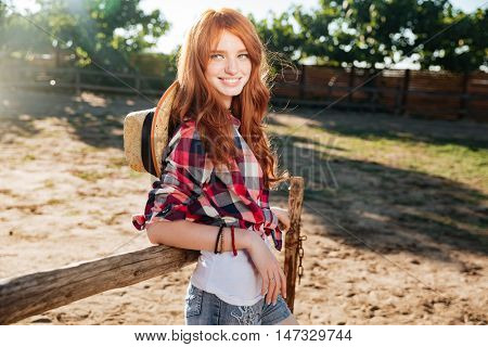Cheerful redhead young woman cowgirl standing in village