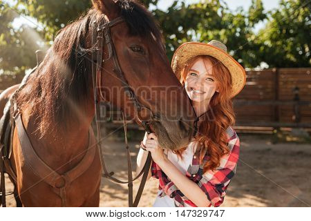 Cheerful lovely young woman cowgirl in hat with her horse in village