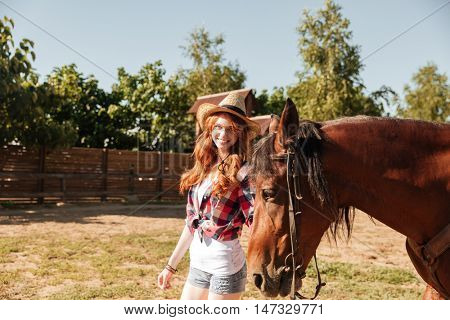 Cheerful young woman cowgirl holding and walking wit her horse on ranch