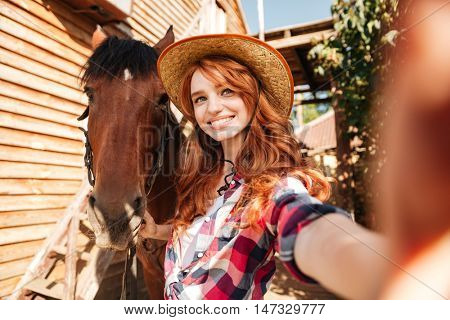 Happy beautiful young woman cowgirl taking selfie with her horse on ranch