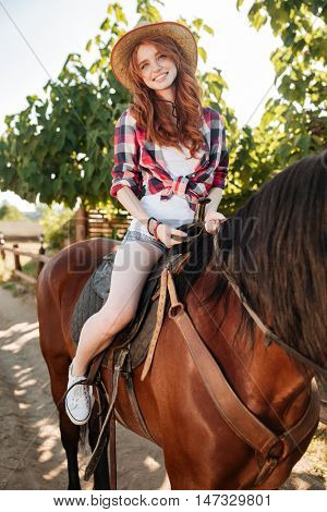 Smiling lovely young woman cowgirl riding horse outdoors in summer