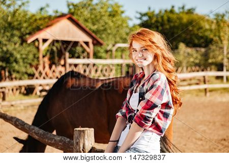 Portrait of cheerful attractive young woman cowgirl with horse in village