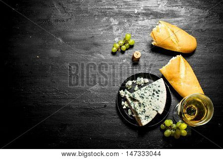 glass of white wine with blue cheese and ciabatta . On a black wooden background.