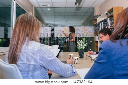 Female coach training business team sitting at table with documents in headquarters