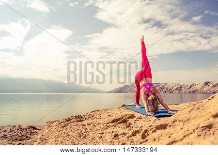 Woman meditating in yoga pose at the sea on rocks. Caucasian blonde girl exercising and training yoga peaceful stretching under cloudy morning sky. Fitness and exercising motivation and inspiration.
