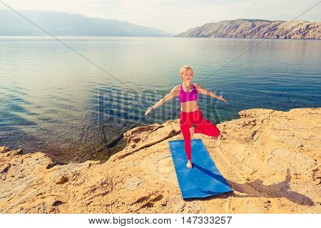 Woman meditating in yoga pose at the sea on rocks. Peaceful blonde girl exercising and training yoga. Female stretching with arms outstretched. Fitness and exercising motivation and inspiration.
