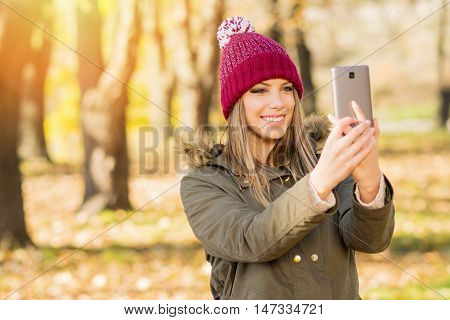 Beautiful young woman in jacket and knitted hat taking a selfie in autumn on smart phone