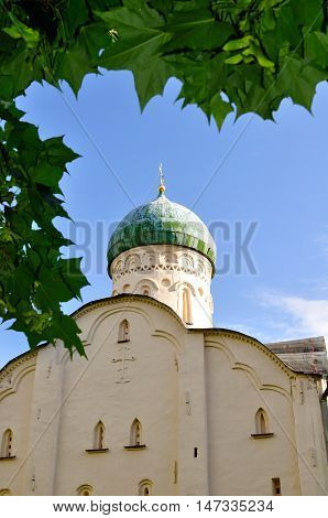 Orthodox church of St Theodore Stratilates on the Brook in Veliky Novgorod Russia - architecture closeup view framed by green leaves