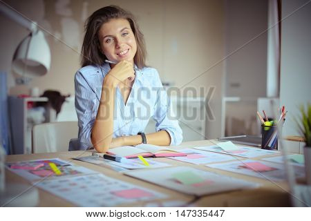 Young woman sitting at the desk with instruments, plan and laptop