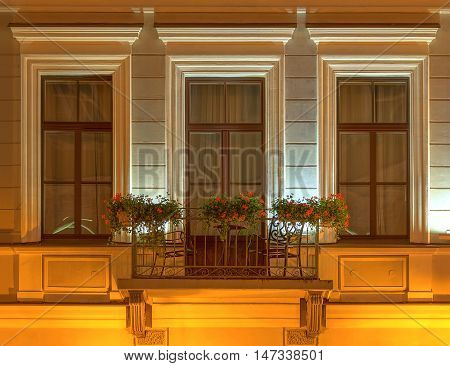 Several windows and balcony in a row on night illuminated facade of the Kempinski Hotel Moika 22 front view St. Petersburg Russia