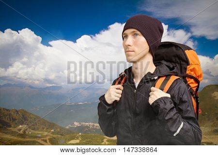 Man hiker on the background of mountain landscape with large cumulus cloud.