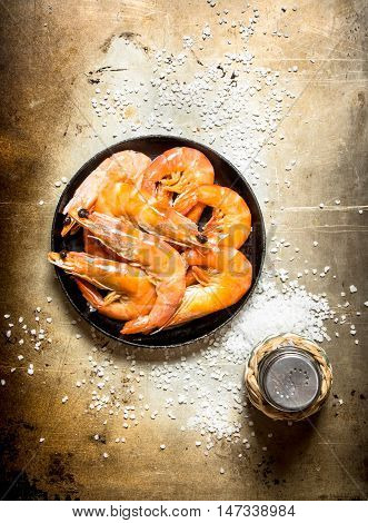 Frying pan with shrimp and salt. On an old rustic background .