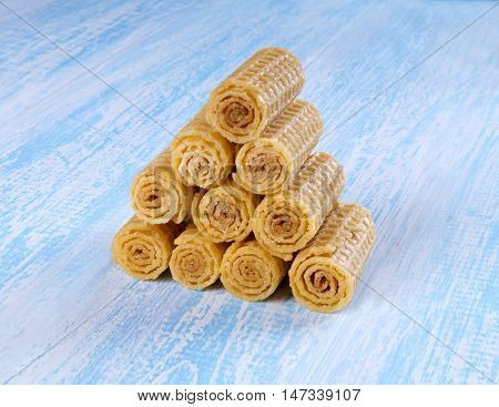 Wafer rolls on a wooden blue background. Wafer rolls are folded house.