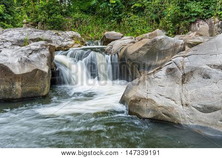 Waterfall cascades flowing over flat rocks in forest.