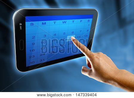 A woman's finger selects a day on a calendar on a digital  tablet