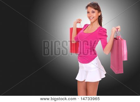 Beautiful woman  shopping  over dark gray background