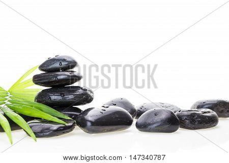 Stack Of Black Wet Basalt Balancing Stones And Green Leaf, On White Background.