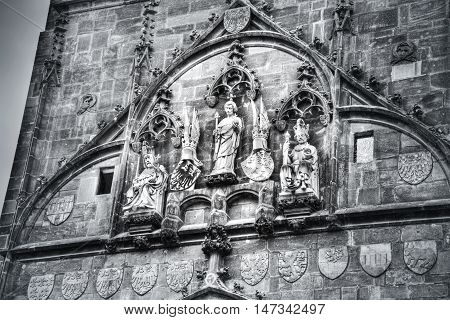 Charles Bridge gate in Prague. Statues on the gate. Black&white picture.