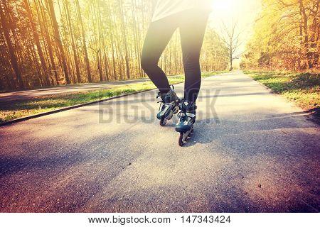Teenage girl on roller skates at summer. Inline skates sport conceptual image.