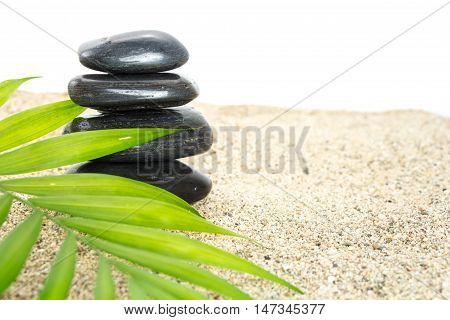 Stack Of Black Basalt Balancing Stones On Sand With Green Leaf, On White Background.