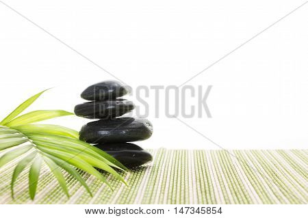 Stack Of Black Basalt Balancing Stones With Green Leaf On Bamboo Mat, On White Background.