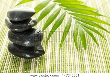 Stack Of Black Basalt Balancing Stones With Green Leaf On Bamboo Mat