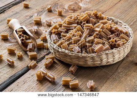 Raw pasta of buckwheat flour in a wicker basket on the old wooden table. Gluten-free products. The source of vitamins and minerals. The concept of healthy and vegetarian food
