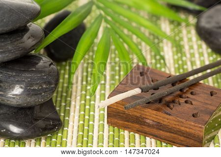 Incense sticks with black basalt stones and green leaf on bamboo mat