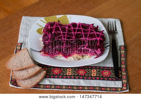 Dressed herring (Ukrainian: Shuba) is a layered salad composed of diced salted herring covered with layers of grated boiled vegetables (potatoes, carrots, beet roots), chopped onions, and mayonnaise.