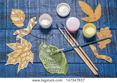 Hand Painted on dry autumn leaves. Gouache brushes and a variety of autumn leaves on a blue wooden table. Children's Art Project