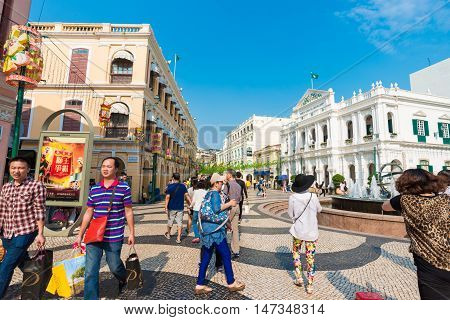 Macau China - October 22 2015: Tourists and shoppers walking along a narrow street with colourful building in central Macau with many shops and restaurants.