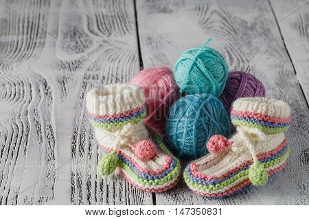 Crochet Baby Booties on white wooden table