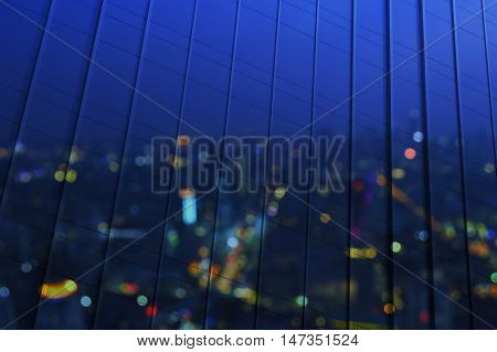 Reflect of blur aerial view of cityscape on modern window office tower night time