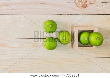 Lemons in a wooden crate on wooden table background.