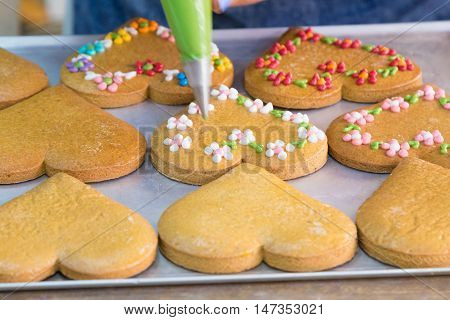 Baked gingerbreads on baking pan are decorated with pastry bag