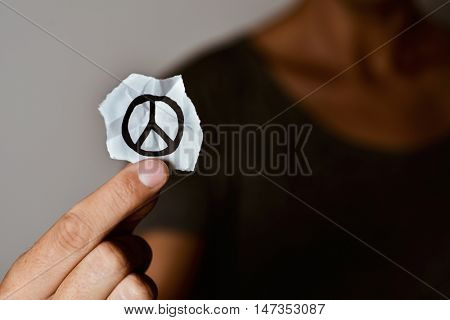 closeup of a young man showing a piece of paper with a peace symbol drawn in it