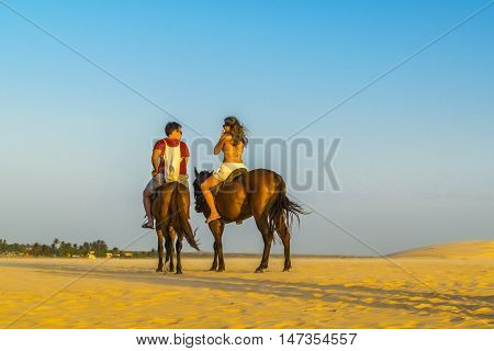 JERICOACOARA, BRAZIL, DECEMBER - 2015 - Couple riding horse at the beach in Jericoacoara Brazil