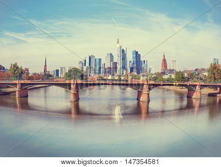 Daytime view of Frankfurt city skyline with Alte Brucke bridge. Creative wide angle effect