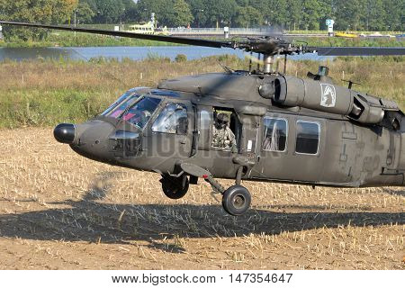 GRAVE NETHERLANDS - SEP 17 2014: American Army Blackhawk helicopter landing in a field.
