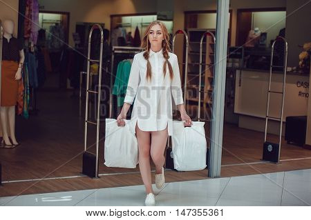 Woman coming out of the store after shopping with bags