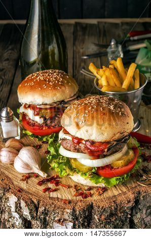 Two burgers with mushrooms tomatoes cucumbers salat cheese and onions on a wooden base with garlic and fries