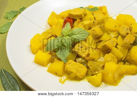 stew meat with potatoes  and vegetables, beef stew yellow garnished with mint leaves