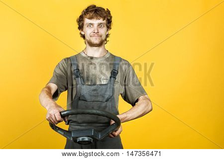 Handsome smiling mechanic in work clothes keeps the wheel like a driving and posing on the background of yellow bright wall