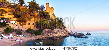 LLORET DE MAR, SPAIN - AUGUST 26, 2016:Landscape of Lloret de Mar Castle and its beach in a sun lights. Spain.