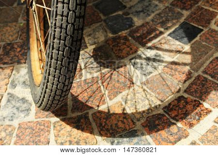 Vintage Motorcycle Wheel Casting Shadow On Cobbled Street