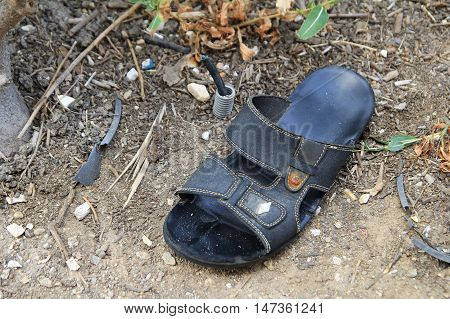 Old lost or abandoned mans sandal on the ground among other rubbish and debris