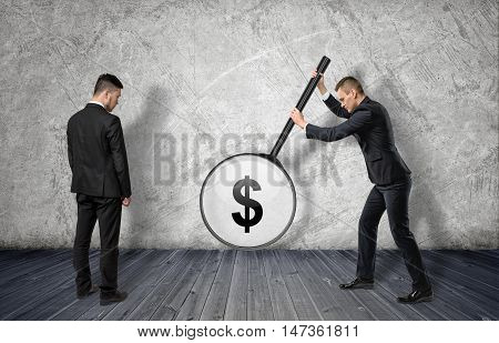 Two businessmen: the right one enlarging dollar sigh with big magnifier, the left one looking at it. Profit and success. Teamwork. Experience and knowledge.