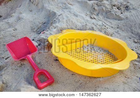 Children plastic strainer and shovel in sandpit