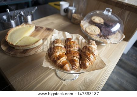 Delicious breakfast with fresh croissants and cake on old wooden background