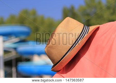 Straw Trilby Hat On Sunny Pool Side With Water Slide In Distance